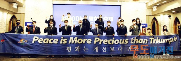 """Attendees holding the GCS slogan """"Peace is More Precious than Triumph"""" banner"""