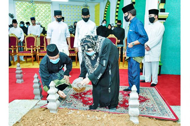 Members of the royal family pour scented water on the prince's grave (Borneo Bulletin)