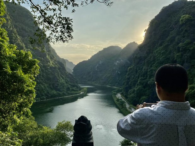 A tourist takes photos of a river in Ninh Binh Province