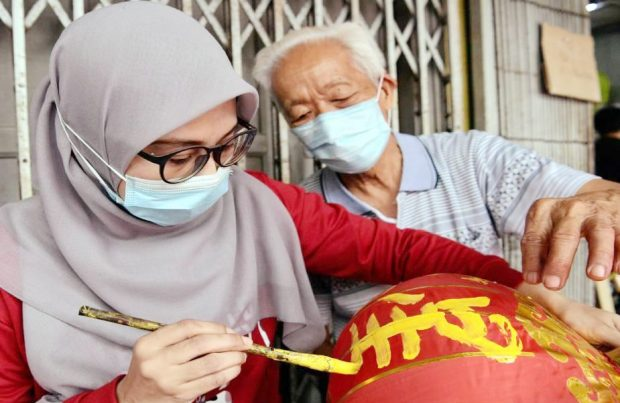 Chinese calligraphy sifu, Ho Chung, 83, giving a finer point on the art of Chinese calligraphy to Azizah Mokhsan, 38, an employee of an air-conditioner shop, on how to transfer the art of calligraphy on a lantern (Bernama)