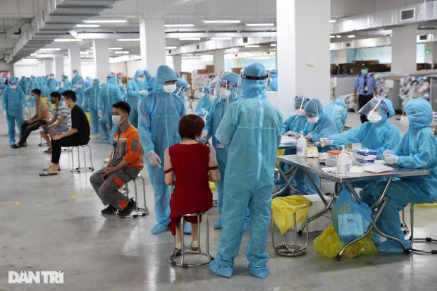 Photo caption: Health workers take samples for Covid-19 testing at an industrial zone in Bac Giang Province. Photo by Quang Vinh