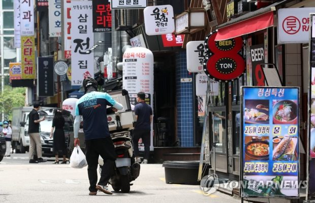 A delivery worker picks up take-out food in central Seoul on July 12, 2021. (Yonhap)