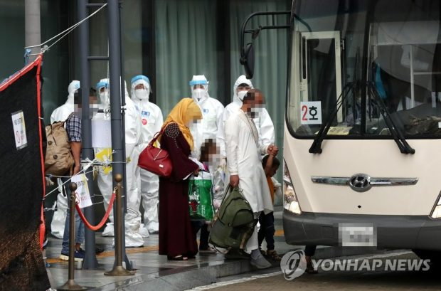 Afghan evacuees get on a bus in Gimpo, west of Seoul, on Aug. 27, 2021, to head for a state-run human resources development center in Jincheon, 91 kilometers southeast of Seoul. About 380 Afghans, who have worked for South Koreans in the war-ravaged nation, and their family members were airlifted to South Korea the previous day. (Yonhap)