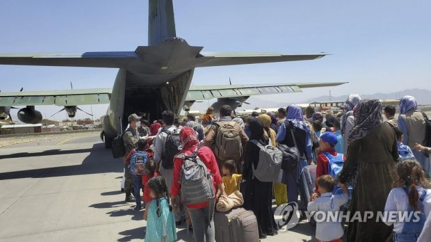 Some 380 Afghans who have worked for South Koreans in their war-ravaged nation and their family members board a South Korea military plane at an airport in Kabul on Aug. 25, 2021, to head for South Korea, in this photo provided by the Air Force. (Yonhap)