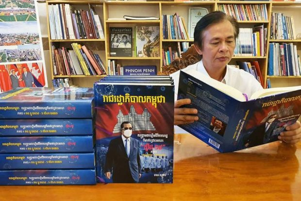 Chhay Sophal with his latest book - a historical record of Cambodia's fight against COVID-19