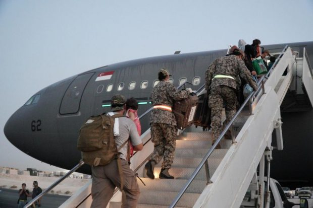 Singapore Army personnel assisting evacuees as they board the A330 MRTT at Al Udeid Air Base in Qatar.